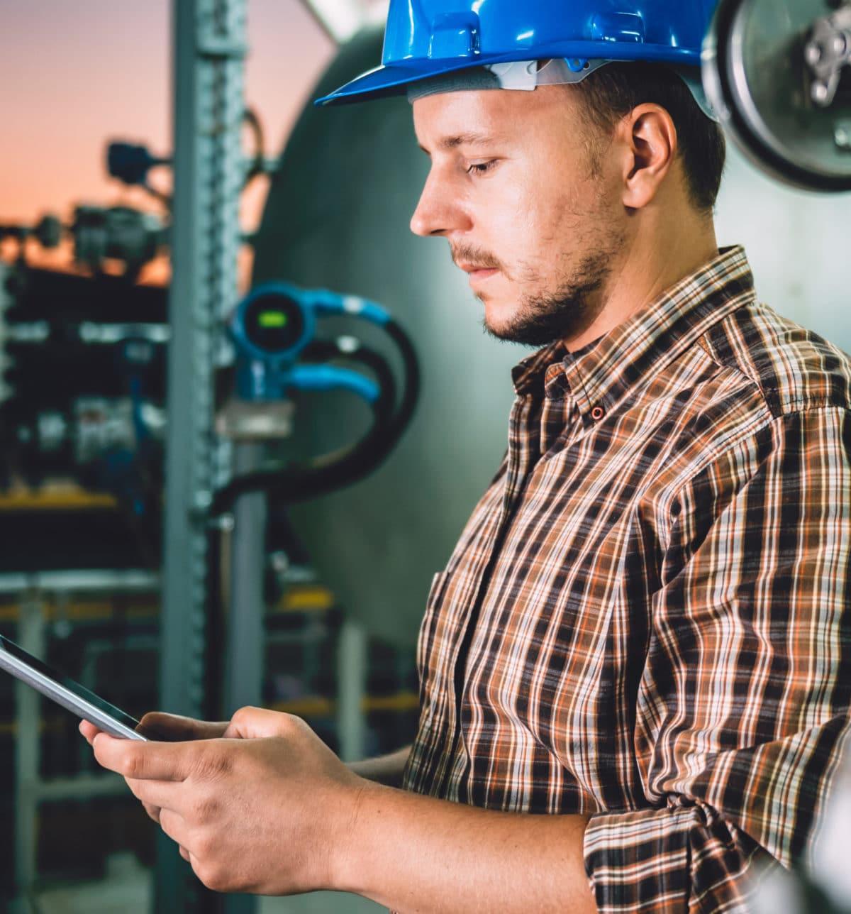 Man wearing blue hardhat using tablet at Natural gas processing facility